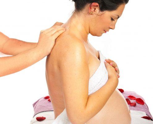 Schwangere Frau erhält eine Rückenmassage